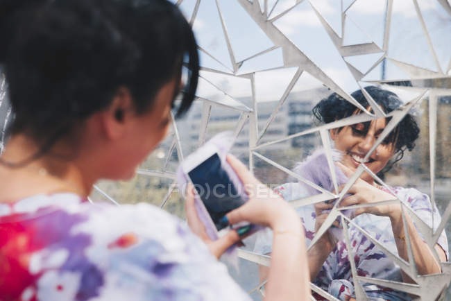 Young woman taking selfie through mobile phone against glass mosaic wall — Stock Photo