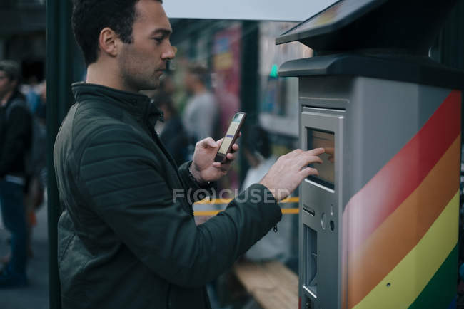 Side view of man touching ATM screen while holding smart phone — Stock Photo