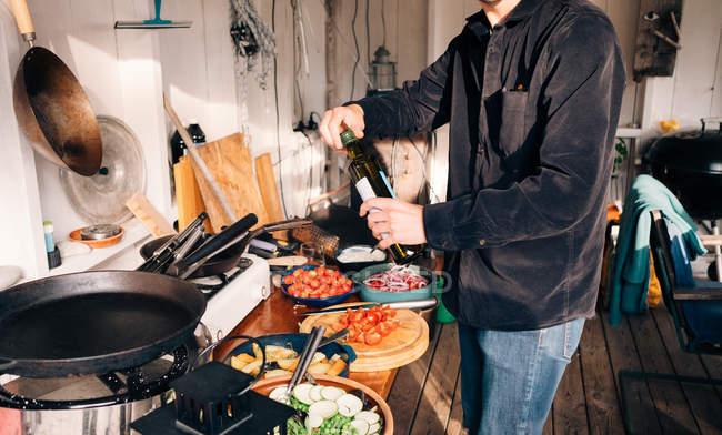 Міделю подання молодий чоловік тримає пляшку оливкова олія кухні — стокове фото