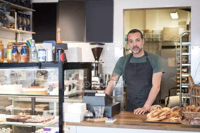 Portrait of confident mature male owner standing at checkout in bakery — Stock Photo
