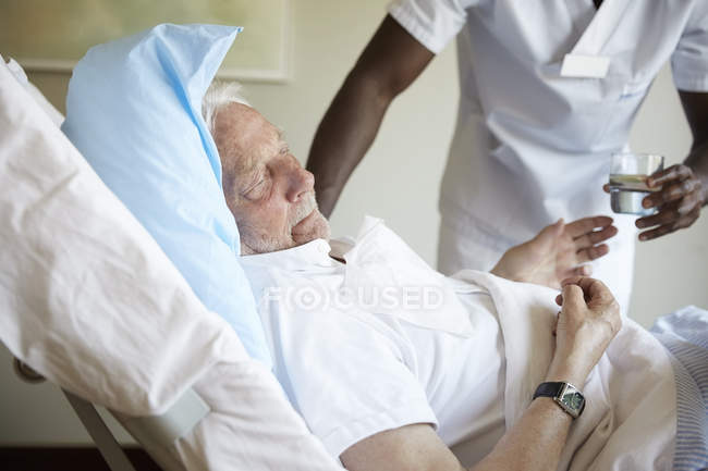 Midsection of male nurse giving drinking water to senior man in hospital ward — Stock Photo