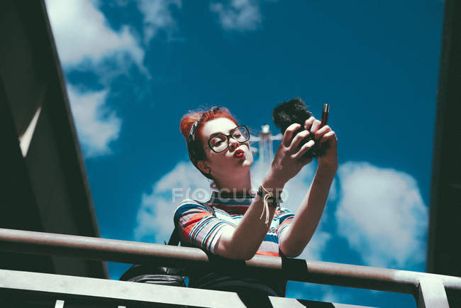 Low angle view of young woman taking selfie with mobile phone while leaning on railing against sky — Stock Photo