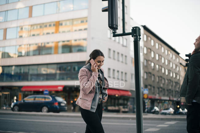 Smiling young woman talking on mobile phone walking against building in city — Foto stock