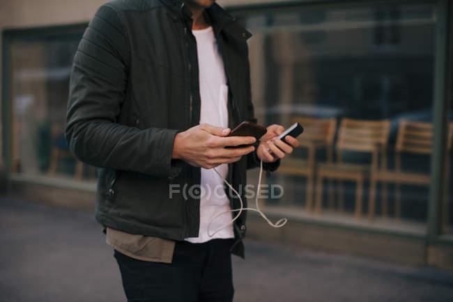 Sezione centrale dell'uomo ricarica smartphone mentre cammina in città — Foto stock