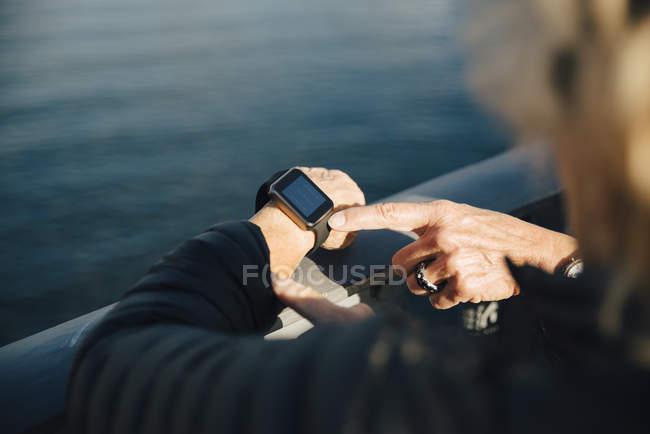 Ausgeschnittenes Bild einer Seniorin mit Smartwatch am Brückengeländer — Stockfoto