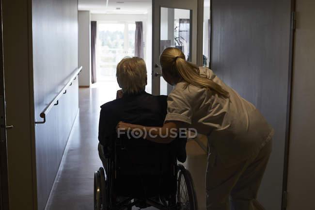 Vue arrière d'une infirmière avec un aîné assis en fauteuil roulant dans le couloir de l'hôpital — Photo de stock