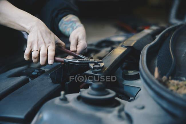 Bild des weiblichen Mechaniker Verschärfung Nuss auf Automotor mit Schraubenschlüssel beschnitten — Stockfoto