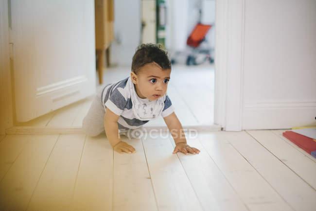 Bambino guardando lontano mentre striscia sul pavimento a casa — Foto stock