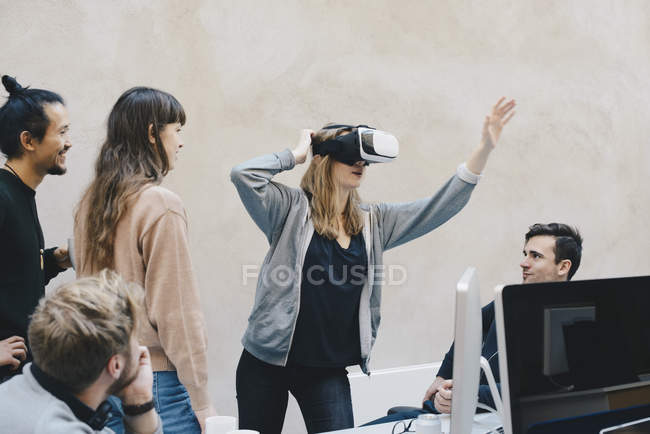 Female computer programmer using VR glasses while standing with colleagues in office — стокове фото