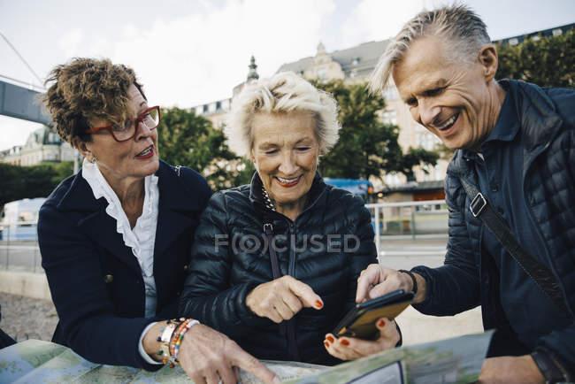 Sénior masculino e feminino amigos com mapa e telefone celular na cidade — Fotografia de Stock