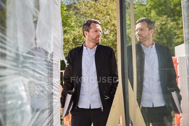Businessman with file reflecting on glass at construction site — Stock Photo