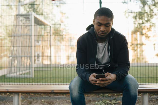 Человек с помощью смарт-телефона, сидя на скамейке против забора — стоковое фото
