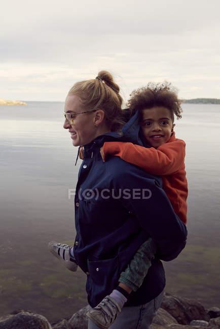 Seitenansicht des Lächelns Mutter, Huckepack auf den Sohn am Seeufer — Stockfoto