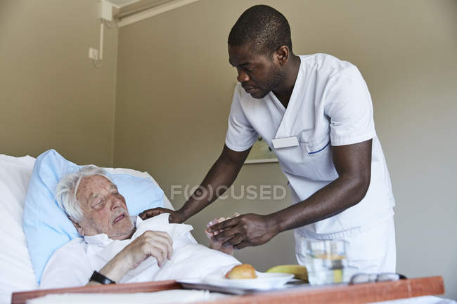Male nurse giving cough syrup to senior man in hospital ward — Stock Photo