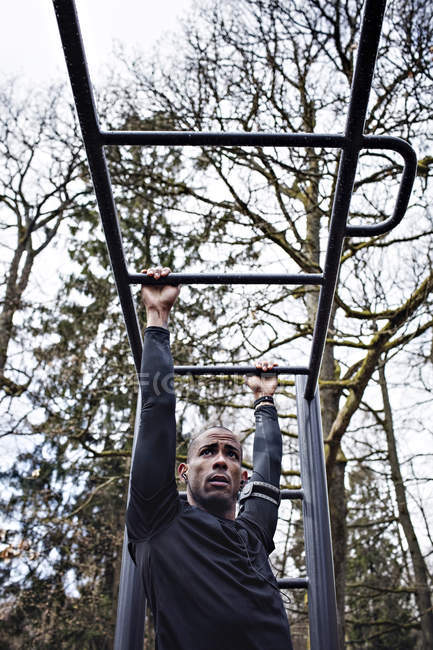 Low angle view of man exercising on monkey bars at outdoor gym — Stock Photo