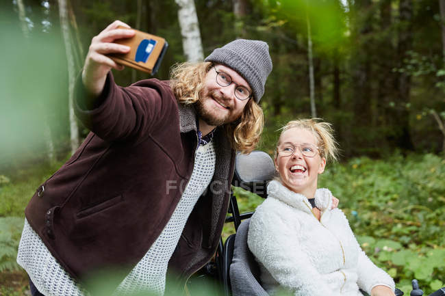 Young male caretaker taking selfie with disabled woman in forest — Stock Photo