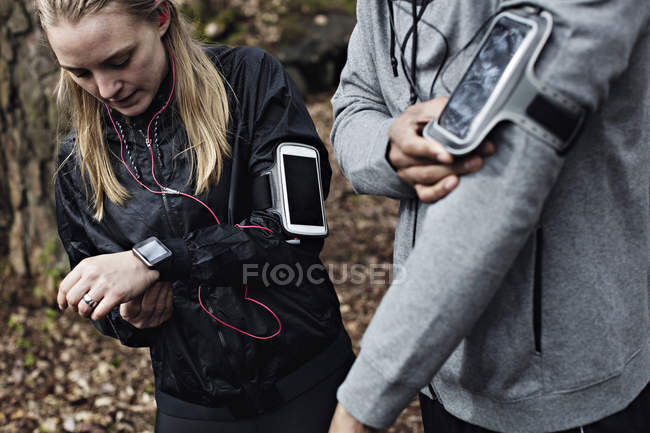 Male and female athletes wearing smart watch and arm band in forest — Stock Photo