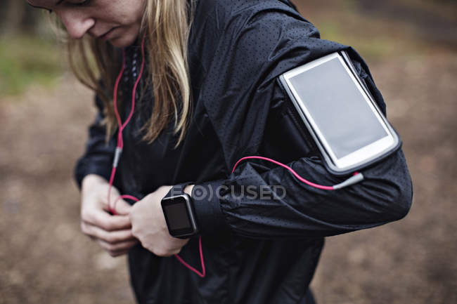 Midsection of female athlete with smart phone in arm band fixing earphones to jacket in forest — Stock Photo
