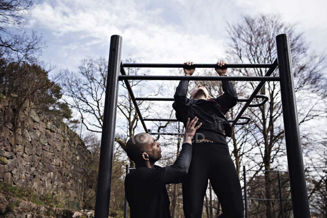Side view of man assisting woman exercising on monkey bars in forest — Stock Photo
