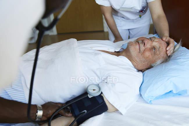 Мужской медсестра, проверку кровяного давления старшего человека на больничной койке, а коллега утешая больного — стоковое фото