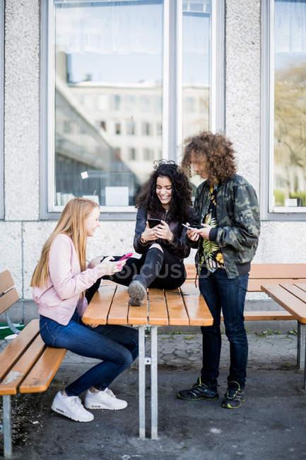 Piena lunghezza di amici felici utilizzando smartphone contro la costruzione — Foto stock