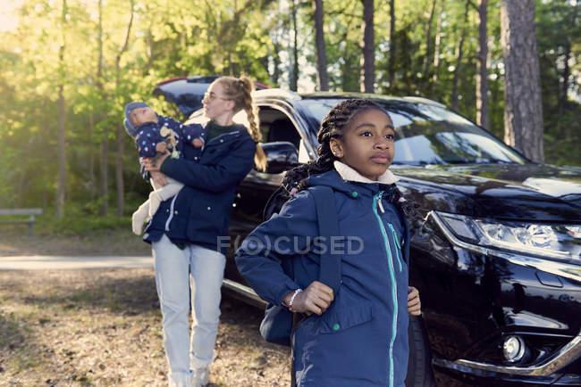 Fille debout contre mère portant bébé garçon en voiture au milieu des arbres — Photo de stock