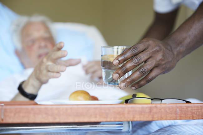 Image recadrée d'une infirmière donnant du verre à boire à un homme âgé dans un service hospitalier — Photo de stock
