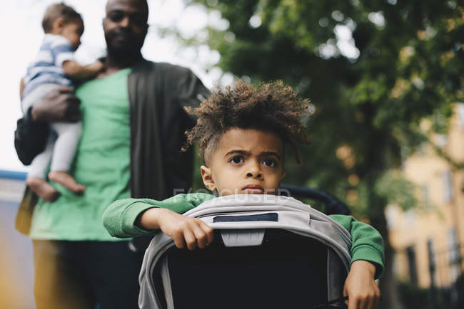 Boy in baby stroller with father and brother in background — Stock Photo