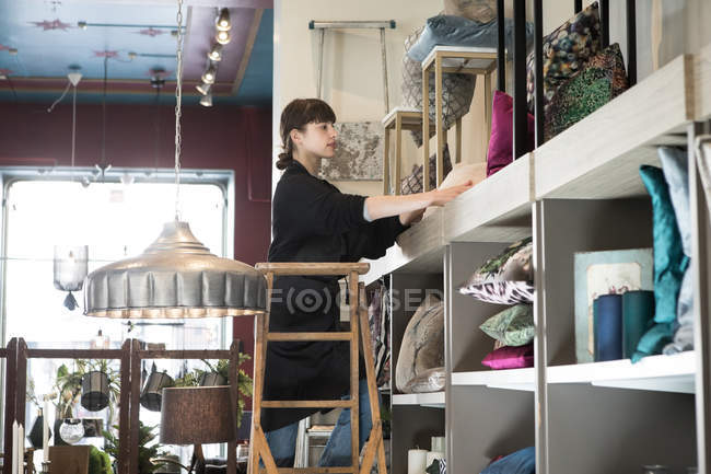 Low angle view of young female owner arranging cushions in rack while standing on ladder at store — Stock Photo