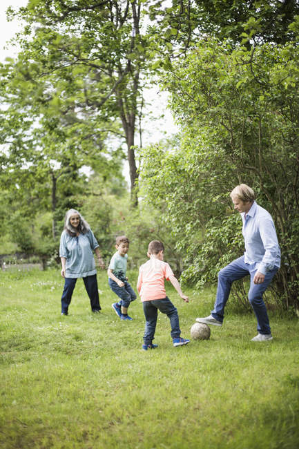 Family playing soccer in back yard — Stock Photo