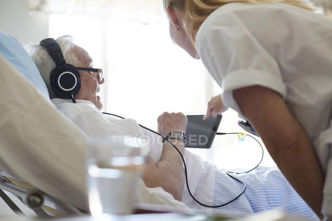Side view of female nurse assisting senior man in using digital tablet on hospital bed — Stock Photo