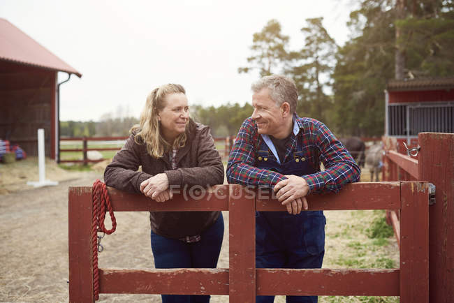 Smiling mature couple looking at each other while leaning on fence in farm — Stockfoto