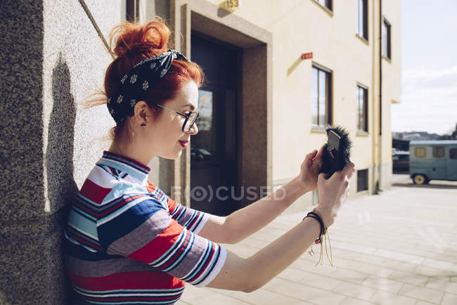 Young female hipster taking selfie while standing against wall — Stock Photo