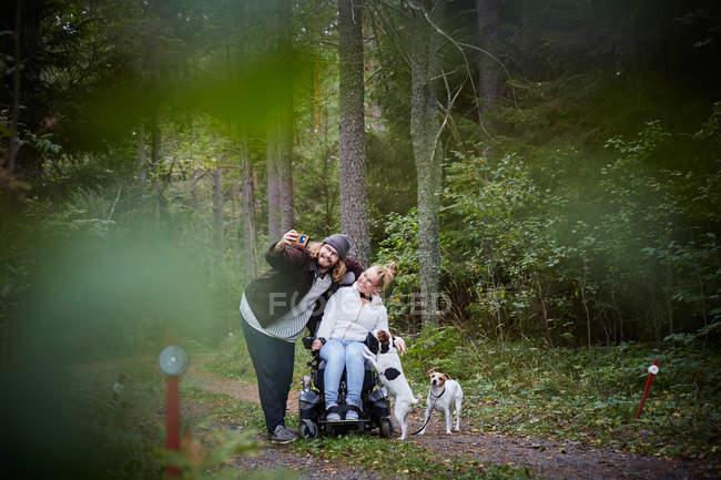 Jeune gardien mâle prenant selfie avec femme handicapée en fauteuil roulant à la forêt — Photo de stock