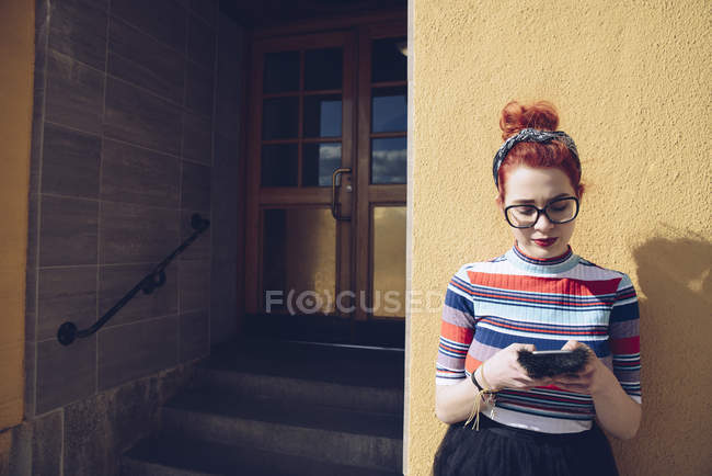 Young female hipster using mobile phone while standing against wall by entrance of building — Stock Photo
