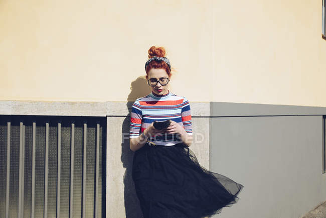 Young female hipster using mobile phone while standing against wall — Stock Photo