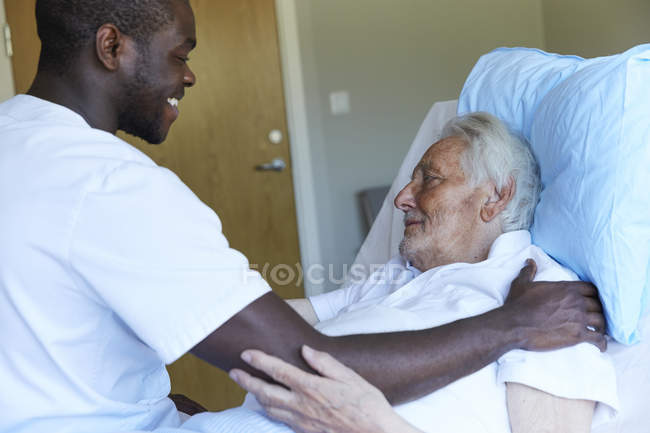 Happy male nurse consoling senior man reclining on bed in hospital ward — Stock Photo