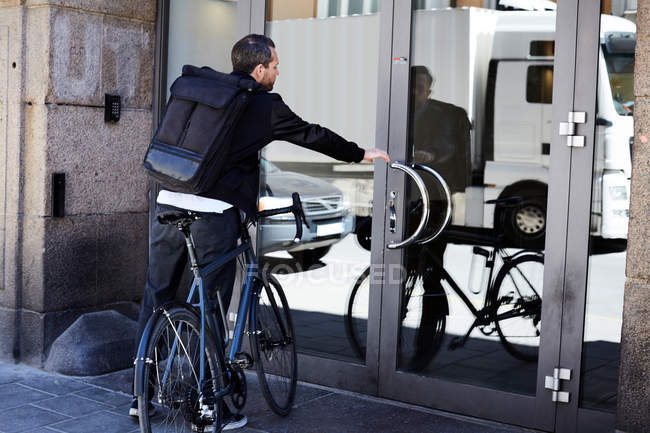 Rear view of businessman with bicycle opening glass door on sunny day — стокове фото