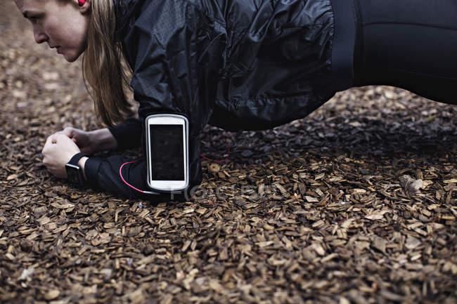 Vista lateral de determinado atleta feminina com telefone inteligente em banda de braço realizando a posição de prancha na floresta — Fotografia de Stock