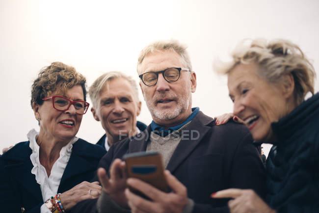 Vista a basso angolo di anziani amici di sesso maschile e femminile utilizzando smartphone mentre in piedi al porto — Foto stock