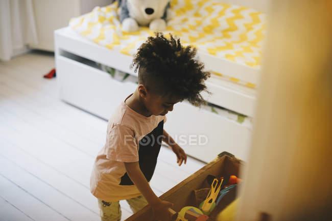 Vue grand angle du garçon jouant avec des jouets à la maison — Photo de stock