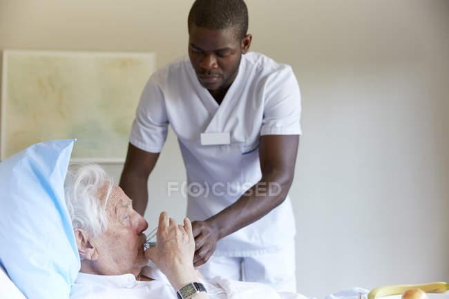 Male nurse feeding water to senior man in hospital ward — Stock Photo