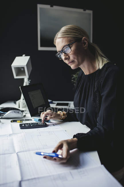 Businesswoman looking at blueprint while using calculator on desk — Stock Photo