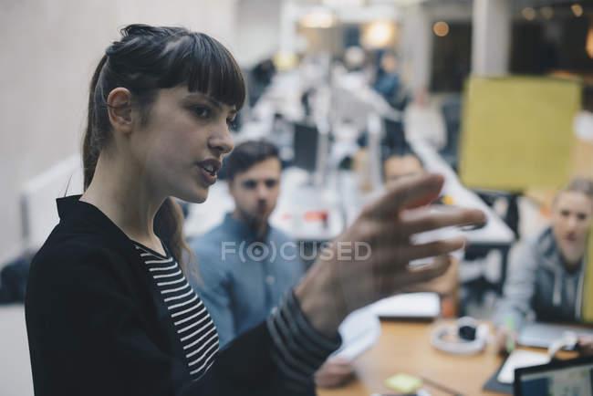 Программист, объясняя Клейкие записки коллег в офисе — стоковое фото