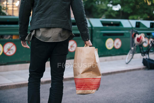 Midsection of man carrying paper bag against garbage cans — Stock Photo