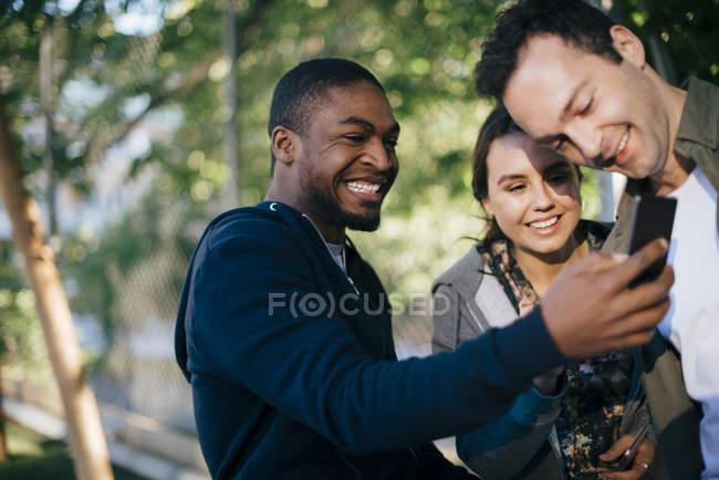 Homem alegre, mostrando o telefone móvel para amigos — Fotografia de Stock