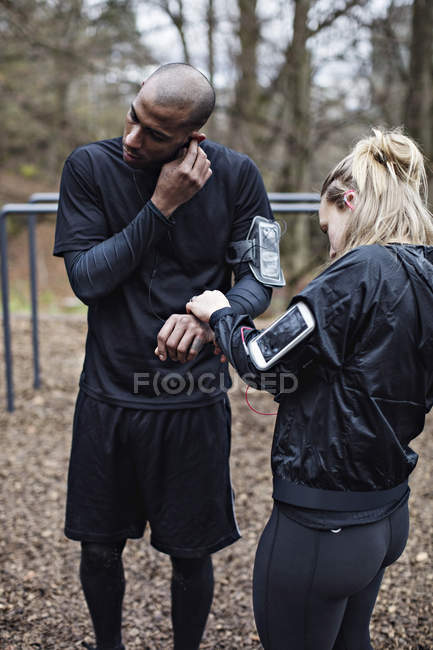Male and female athletes wearing technologies in forest — Stock Photo