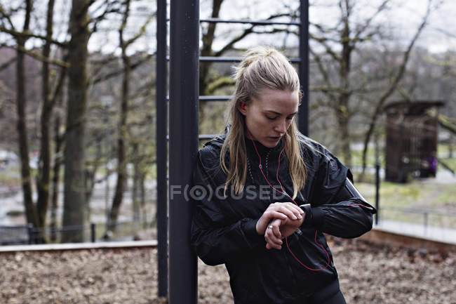 Female athlete checking smart watch while leaning on monkey bars in forest — Stock Photo
