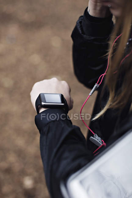 Cropped image of female athlete checking fitness tracker in forest — Stock Photo