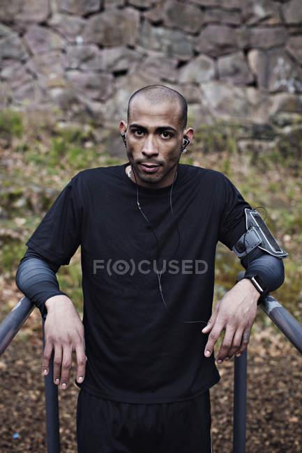 Ritratto di fiducioso atleta maschio che si appoggia sulle barre parallele nella foresta — Foto stock